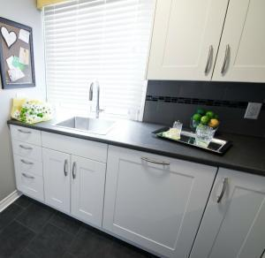 Symmetry White Cabinets and Black Backsplash